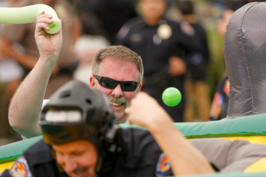 Farmington fire Chief David Burke tries to hit Farmington Police Chief Steve Hebbe with a pool noodle Tuesday during a whack-a-mole activity during National Night Out at Berg Park in Farmington.