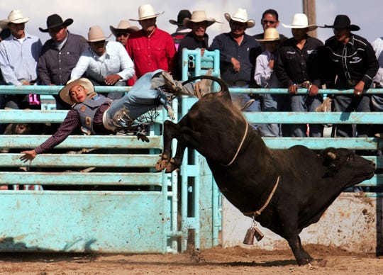 In a file photo dated, Sunday, Oct. 5, 2013, Michael Montague of Standing Rock, N.M., rides Slammin Sosa during the bull riding competition at the 97th Annual Northern Navajo Nation Fair in Shiprock..