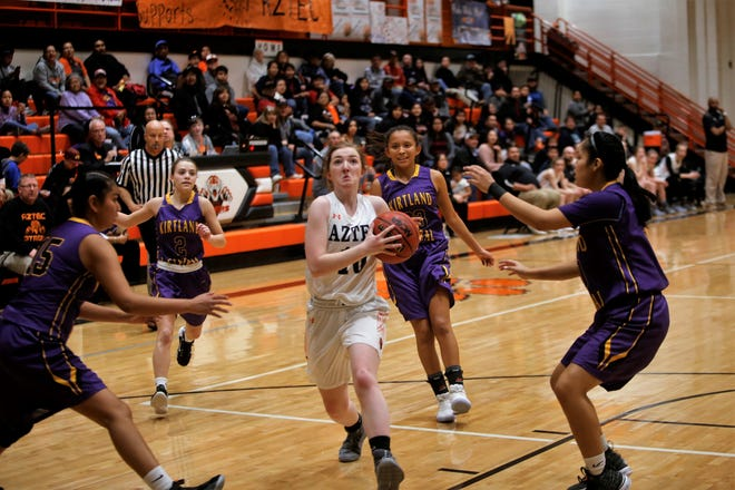 Aztec's Jessi Gillentine drives past a quartet of Kirtland Central defenders for a layup during a district game on Feb. 3 at Lillywhite Gym. The Tigers will open the new season at the Al Armendariz Classic on Nov. 29 at Capital.