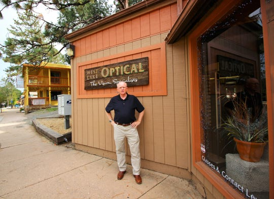 Sam Johnson O.O. stands in front of a sign that he brought to Ruidoso with him from his previous business.