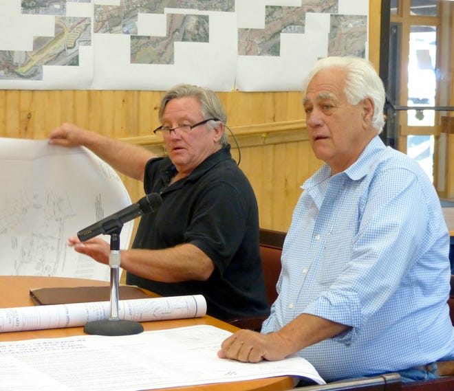 Ruidoso  building inspector Dave Myers, left, and developer Ray Eidson go over plans with commissioners.