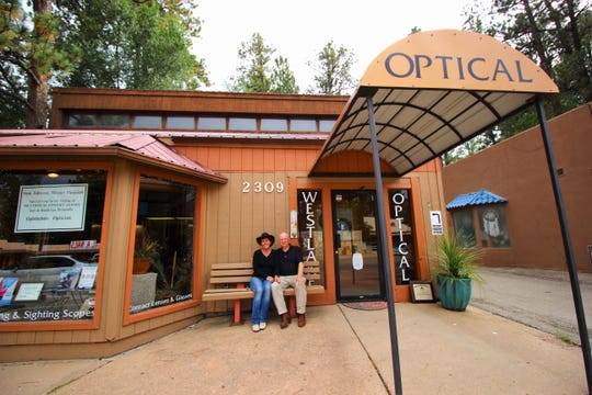 Sam and Michelle Johnson sitting in front of their business. The couple are happy to be living in Ruidoso.