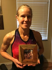 Proudly holding a photo taken with friend Karen Perzyk is Royal Oak's Nikki Derrick. The photo was taken at the 2016 Hawaii Ironman.