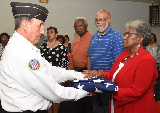 Pat Mason-Guillory accepts the American Flag  from a member of the Acadiana Veterans Honor Guard during a tribute to the United States Armed Forces hosted by the St. Landry Parish Veterans Memorial committee members.