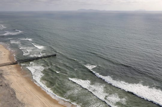 The U.S.-Mexico border fence, seen from above, stretches into the Pacific Ocean on May 11, 2017 in San Diego, California. The fence separates San Diego, California (R), from Tijuana, Mexico (L).