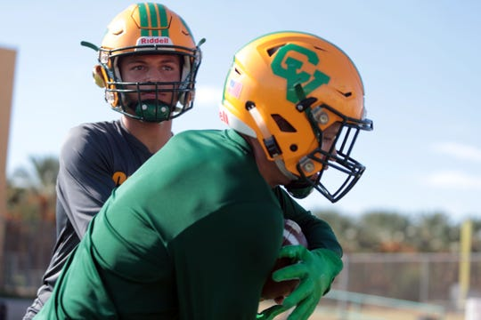 Coachella Valley quarterback Donny Fitzgerald hands off the ball to his brother Angelo Fitzgerald during team practice on Tuesday, October 2, 2018 in Thermal.