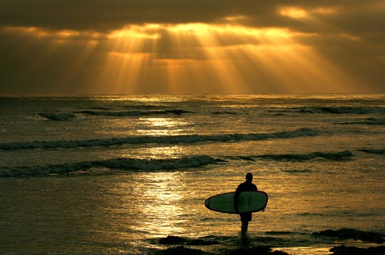 Surfer Ed Folsom exits the water as the sun sets through low clouds on June 23, 2005 at Cardiff State Beach in Cardiff-By-The-Sea, California.