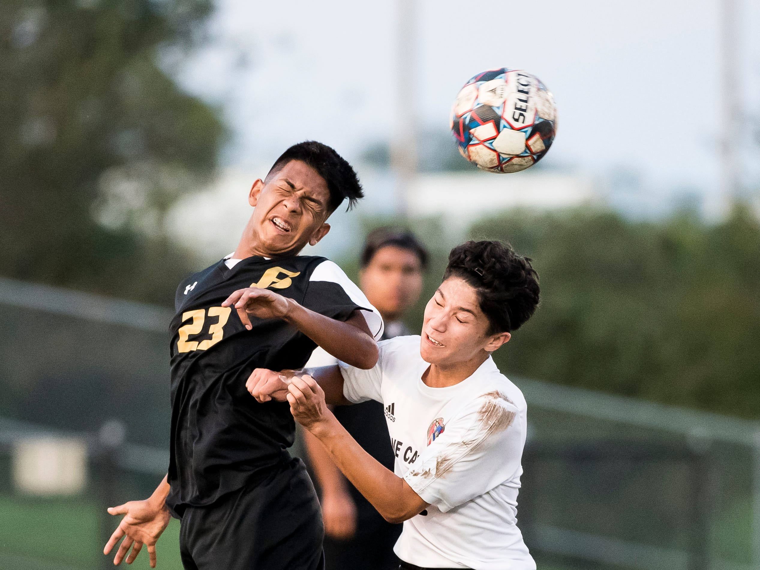 Biglerville's Carlos Castillo (23) hits a header over Delone Catholic's Patrick O'Donnell on Wednesday, October 3, 2018. The Canners won 3-0.