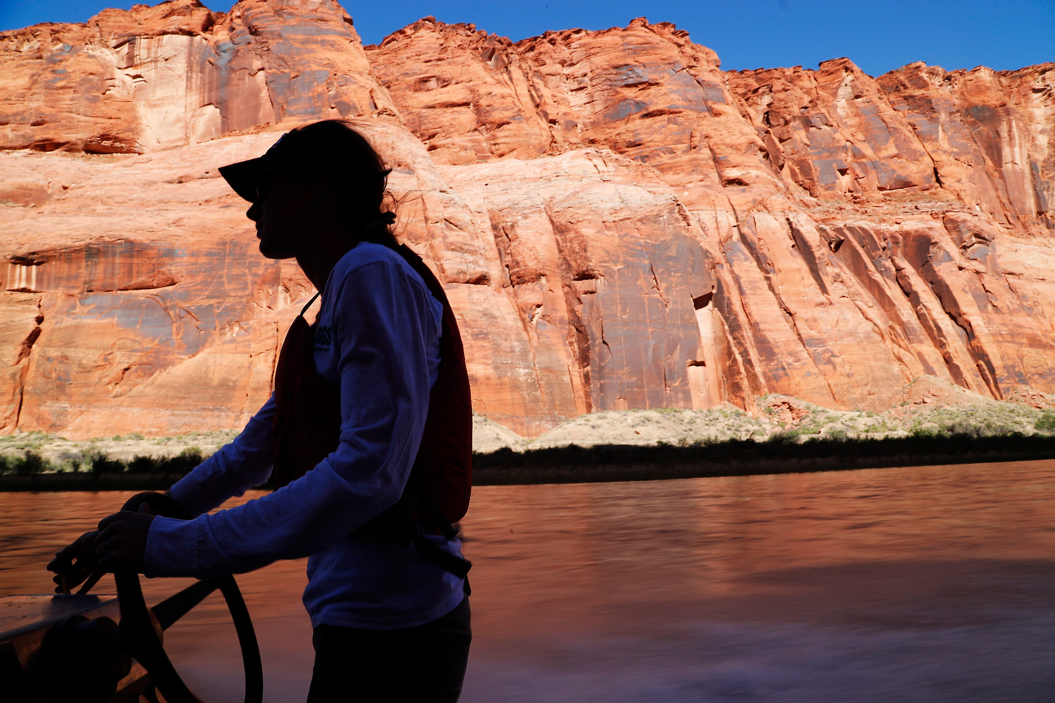 U.S. Geological Survey biologist Megan Daubert navigates the Colorado River while collecting bug traps near Marble Canyon. Experts say the river's insect population offers less nourishment to go around than a healthy environment would provide.