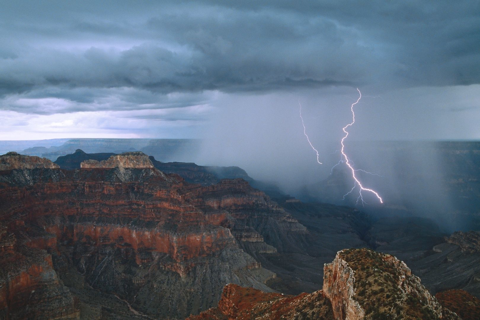 Lightning arcs into Grand Canyon near Point Sublime on the North Rim.