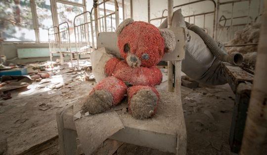 Un viejo oso de peluche rojo sentado en una silla en un jardín de infancia abandonado en Pripyat, un recordatorio del desastre de Chernobyl en 1986.