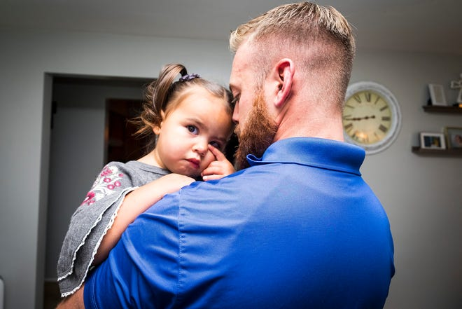 River, 2, rubs her eye while her father Robbie Roche holds her Tuesday, Oct. 2, 2018 in the living room of their Port Huron house. River has DIPG, and her parents have organized fundraisers to help cover the costs of her treatment.