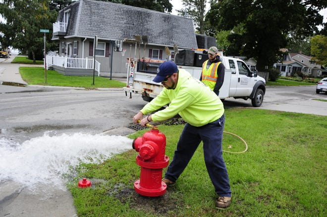 Marc Seacat opens a fire hydrant at Armour and Holland streets as Jordan Stockwell watches. Port Huron workers are flushing hydrants and water mains.