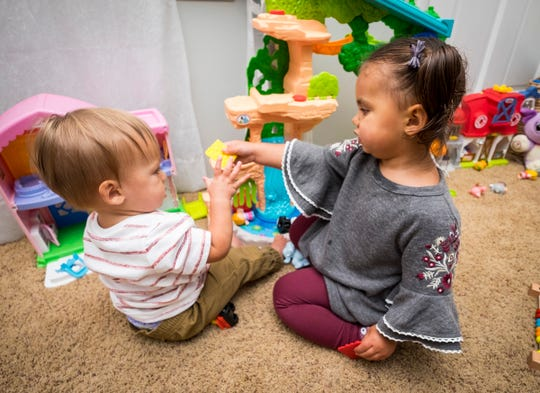 River Roche, 2, plays with her 9-month-old brother Atlas in the living room of their family's Port Huron home Tuesday, Oct. 2, 2018.