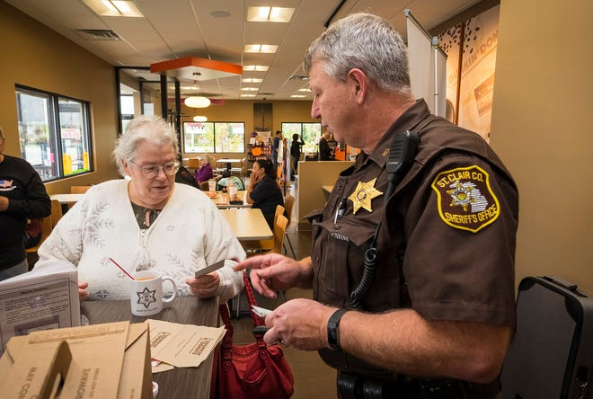 St. Clair County Sheriff Deputy Steve Campau, right, hands a business card to Pamela Dore while they talk over coffee Wednesday, Oct. 3, 2018 during Coffee with a Cop at Dunkin Donuts in Fort Gratiot.