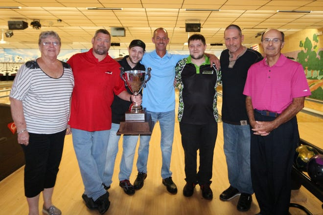 Danny Sneddon of Colony Park North Team No. 2, second from left, holds the Mike Elicker Memorial Traveling Cup, which was presented by Judy Elicker, left. The trophy was presented after the Colony Park North team won the first York Area Bowling Proprietors Association Team Challenge. Don Smith, the Team Challenge director, right, looks on. Sneddon's teammates, from left to right next to Sneddon, are Joey Mong, Chuck Crone, Justin Mong and Dave Rishel.