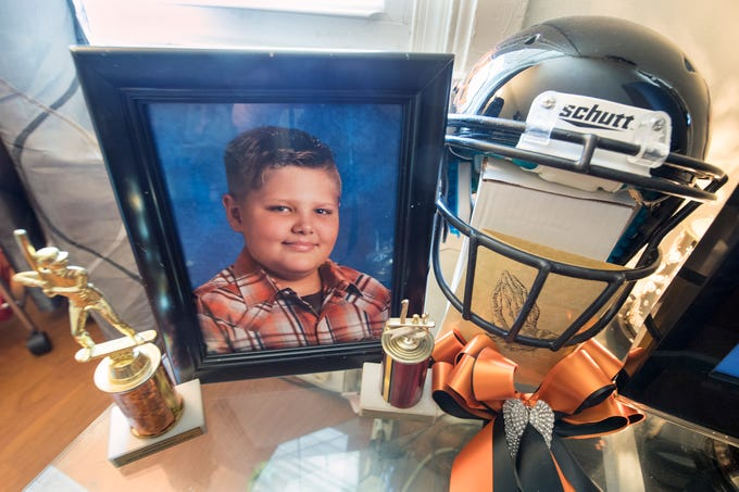 Aportrait of Ashton Potts with his helmet and trophies at his mother's home in York.
