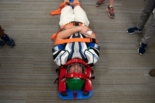 York Daily Record reporter John Buffone lays on a stiff board after athletic training students demonstrated how to lift a player with a back or neck injury during an open house at the Jeanne and Edward H.Arnold Health Professionals Pavilion, Tuesday, Oct. 2, 2018. The Jeanne and Edward H. Arnold Health Professions Pavilion opened officially Wednesday, Aug. 22, as the new home of Lebanon Valley College's Athletic Training, Exercise Science and Physical Therapy programs.