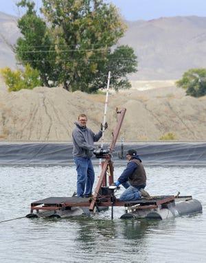 Public Works Director Jay Flakus measures sludge as Ryan Huntley steers.