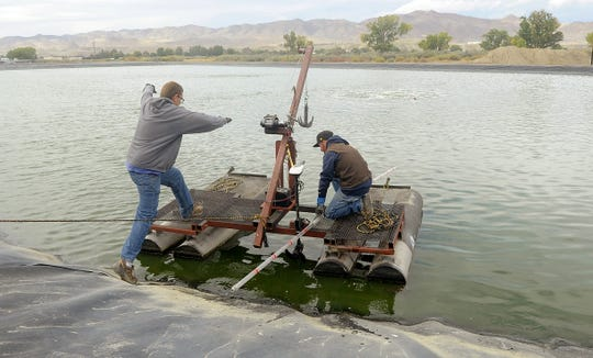 """Public Works Director Jay Flakus jumps onto the """"Shitanic"""" as Ryan Huntley prepares to launch the boat."""