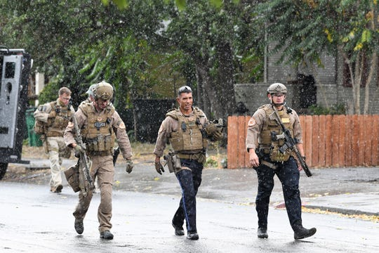 Members of the Reno Police Department SWAT team walk down the center of Park Street near downtown Reno as rain begins to fall on the afternoon of Oct. 3. Police had just taken a man into custody who had been connected to an early-morning shooting the same day.