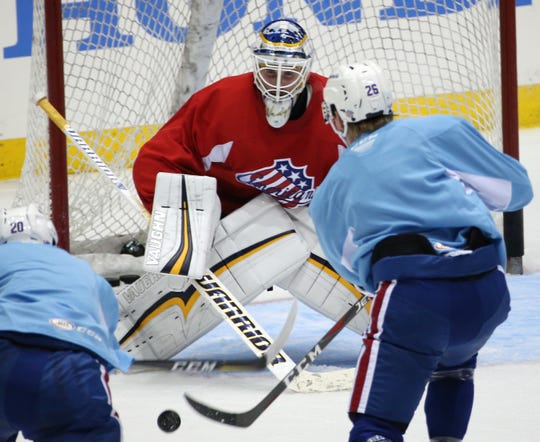 Amerks  goalie Scott Wedgewood attempts to stop a shot by Rasmus Asplund during practice as Eric Cornel, left, heads to the net in practice on Wednesday.