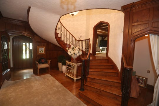 A curved staircase leads to a second level.