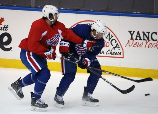 Amerks defenseman Brandon Hickey, left, tries to move left wing C.J. Smith off the puck during practice on Wednesday.