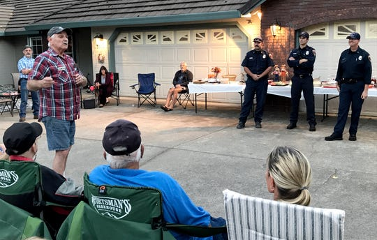 Ron Girard, left, speaks to Harlan Drive residents and Redding firefighters Jason Foley, Andy Kofford and Mike Gould at a National Night Out gathering. The Carr Fire destroyed Girard's home July 26 but he said he's rebuilding in the neighborhood.