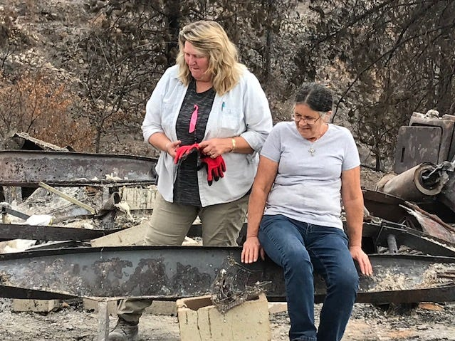 Marci Fernandes sits on the metal frame of her destroyed house, which helped protect the cremated ashes of her late husband, Larry Allen. Lynne Engelbert, canine search specialist with the Institute of Canine Forensics, looks on.