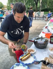 Harlan Drive resident Donovan Lee and son Carson attend Tuesday evening's potluck for National Night Out.