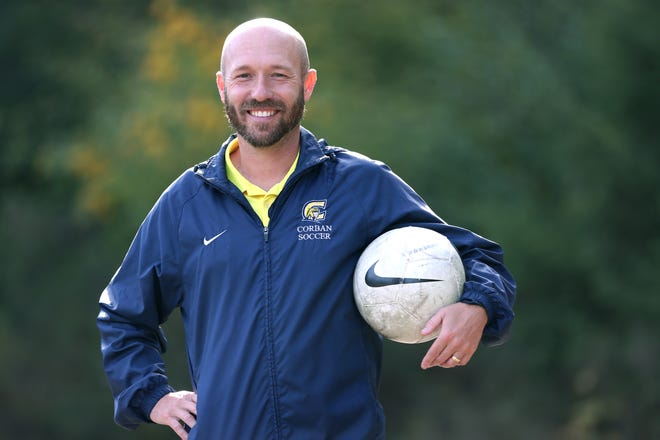 Corban University men's soccer coach Aaron Lewis poses near the team's practice field on Wednesday, Oct. 3, 2018. Lewis has led the Warriors to five consecutive NAIA National Championships appearances.