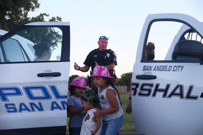 Officer Al Alvarez with the San Angelo Police Department talks with residents during the National Night Out event at Goodfellow Family Housing, Tuesday, Oct. 2, 2018.