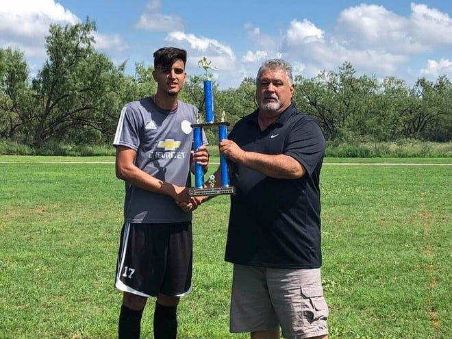 Former Lake View High School soccer star Jordan Reyes receives a trophy for scoring the most goals in a club league.