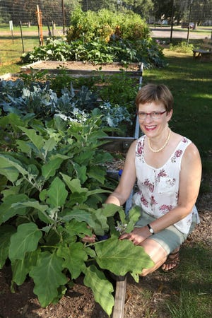 The Rev. Kathryn Reid Walker poses in the First Presbyterian Church community garden in Eau Claire, Wis. on Sept. 13, 2018. The congregation has donated about 250 pounds of produce grown in the garden, which was first planted this year.