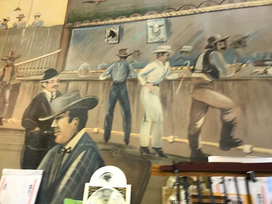 Cowboys stand at a bar in the Arc Light Saloon in this painting. In 1919, the saloon closed and now it is the Heritage Haus.