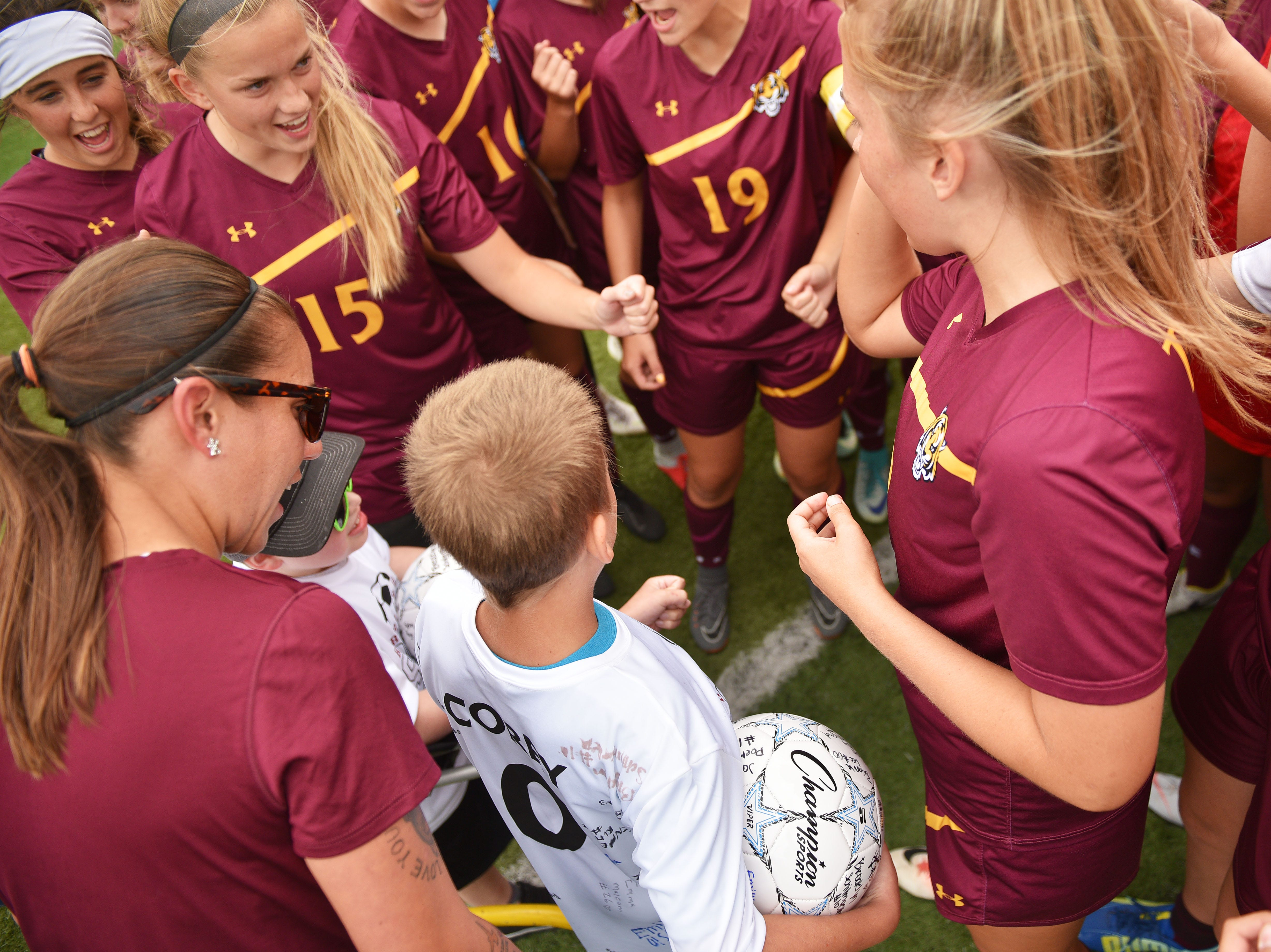 Corey Surikov and Grant Hamilton get in a huddle with the Harrisburg girls soccer team before the game against Hurron Thursday, Sept. 13, at Harrisburg. Corey Surikov and Grant Hamilton were named Players of the Game.