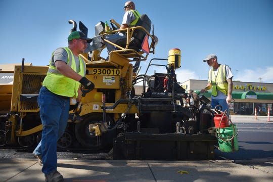 City of Sioux Falls street department Jon Voigt, from left, operator Ryan Sinding and Ben Schaaf repave Minnesota Ave Wednesday, Oct. 3, near downtown Sioux Falls.