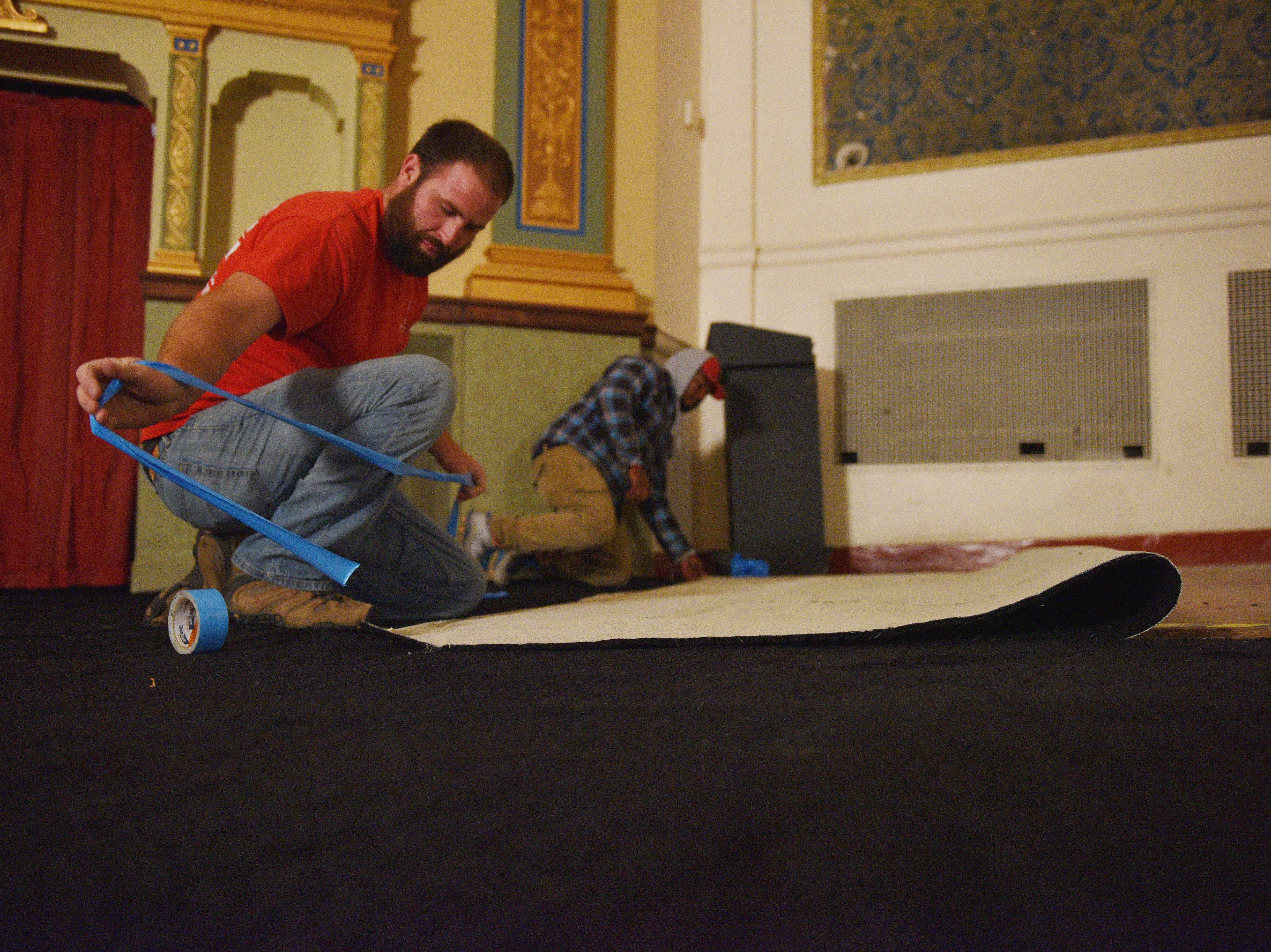 ABC Rental employees Tyler Busch, left, and Desean Waters, right, lay out carpet for the State Theatre prior to the open house on Tuesday, Oct. 2, in downtown Sioux Falls. The State Theatre has been undergoing updates and renovations for years.