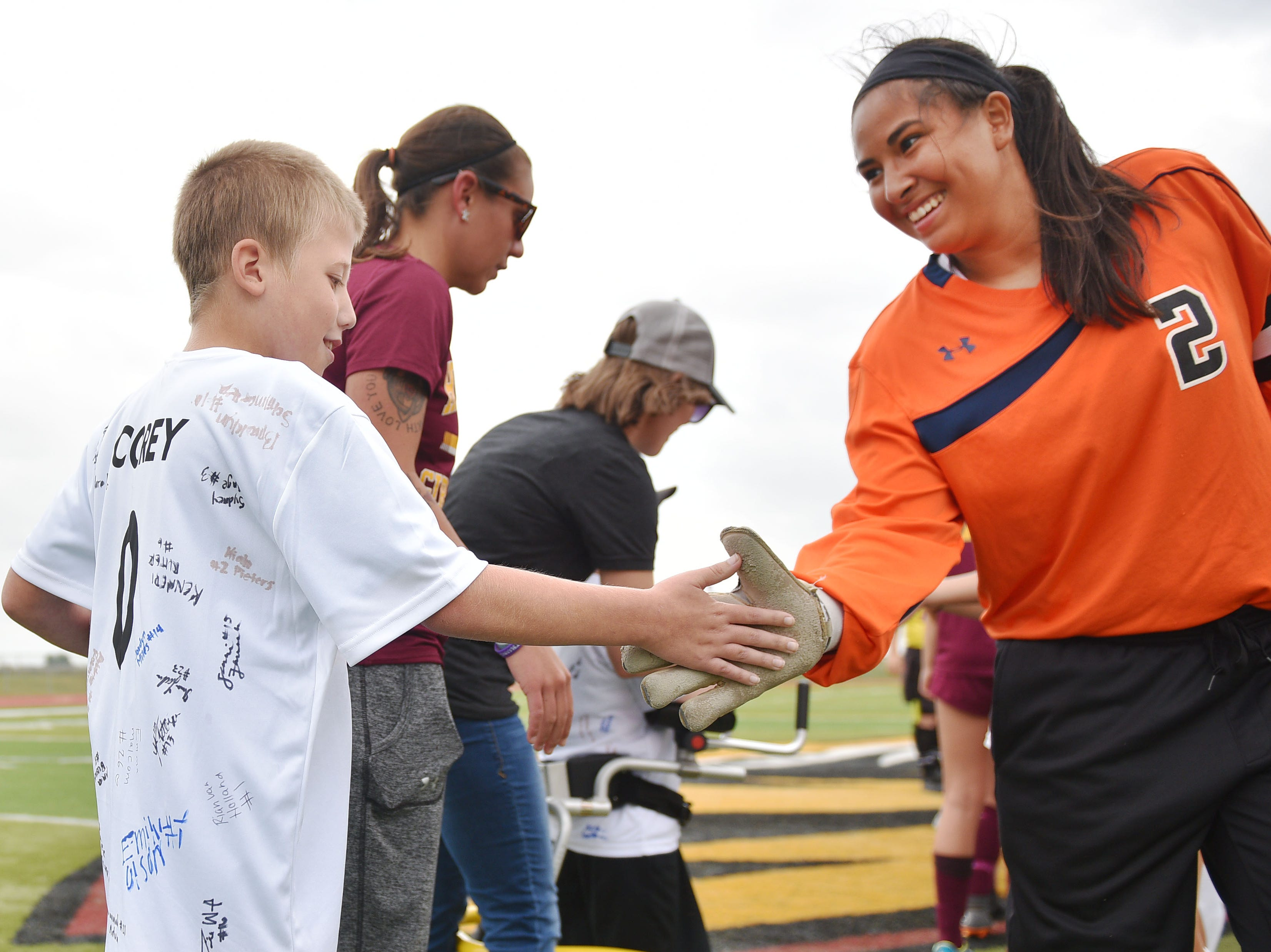 Corey Surikov high fives Hurron's goalie Fatima Reyes before the game against Hurron Thursday, Sept. 13, at Harrisburg. Corey Surikov and Grant Hamilton were named Players of the Game.