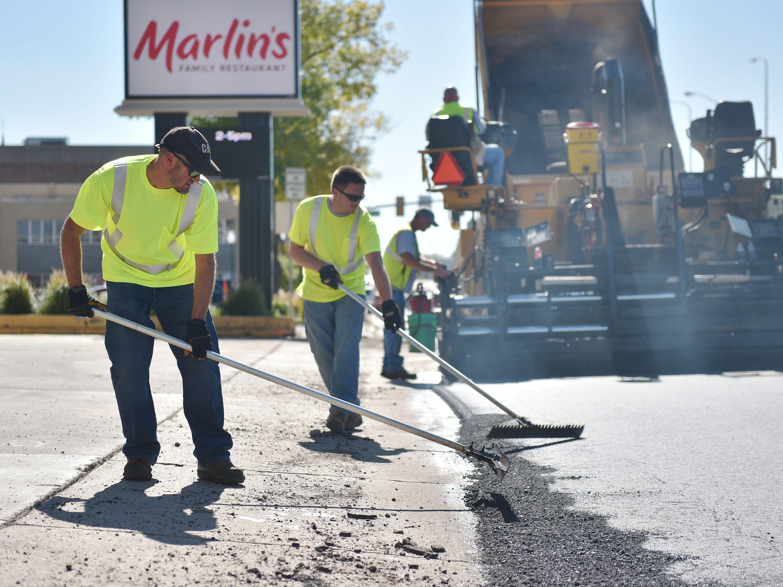 City of Sioux Falls street department Kevin Eschenbaum, left, and Ryan Heald, center, repave Minnesota Ave Wednesday, Oct. 3, near downtown Sioux Falls.