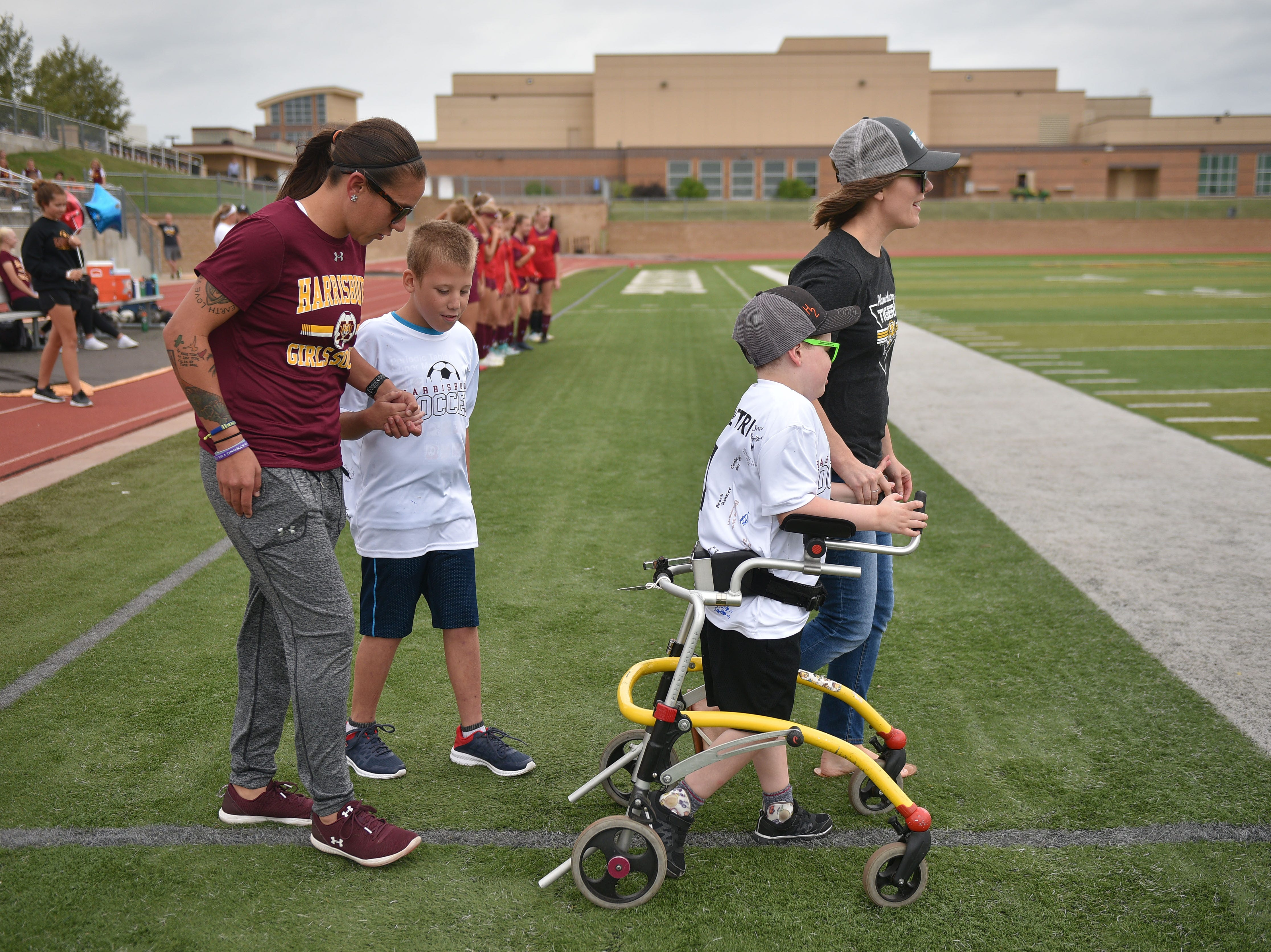 Kate Hamilton walks onto the field with her son Grant and Harrisburg head coach Desiree Parmenter walks out with Corey Surikov before the Harrisburg vs Hurron game Thursday, Sept. 13, at Harrisburg. Grant Hamilton and Corey Surikov were named Players of the Game.