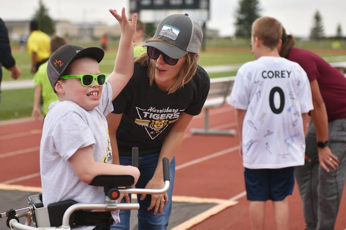 Kate Hamilton tells her son Grant Hamilton to wave to their family in the stands before the Harrisburg vs Hurron game Thursday, Sept. 13, at Harrisburg. Grant Hamilton and Corey Surikov, back right, were named Players of the Game.