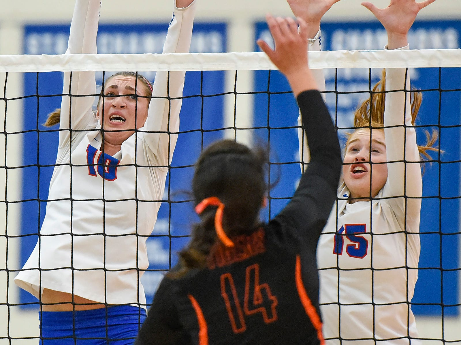 Apollo's Haley Schleper and Sarah Bennett go up to block a spike by Tech's Jessica Schoborg during the second game Tuesday, Oct. 2, at Apollo High School.