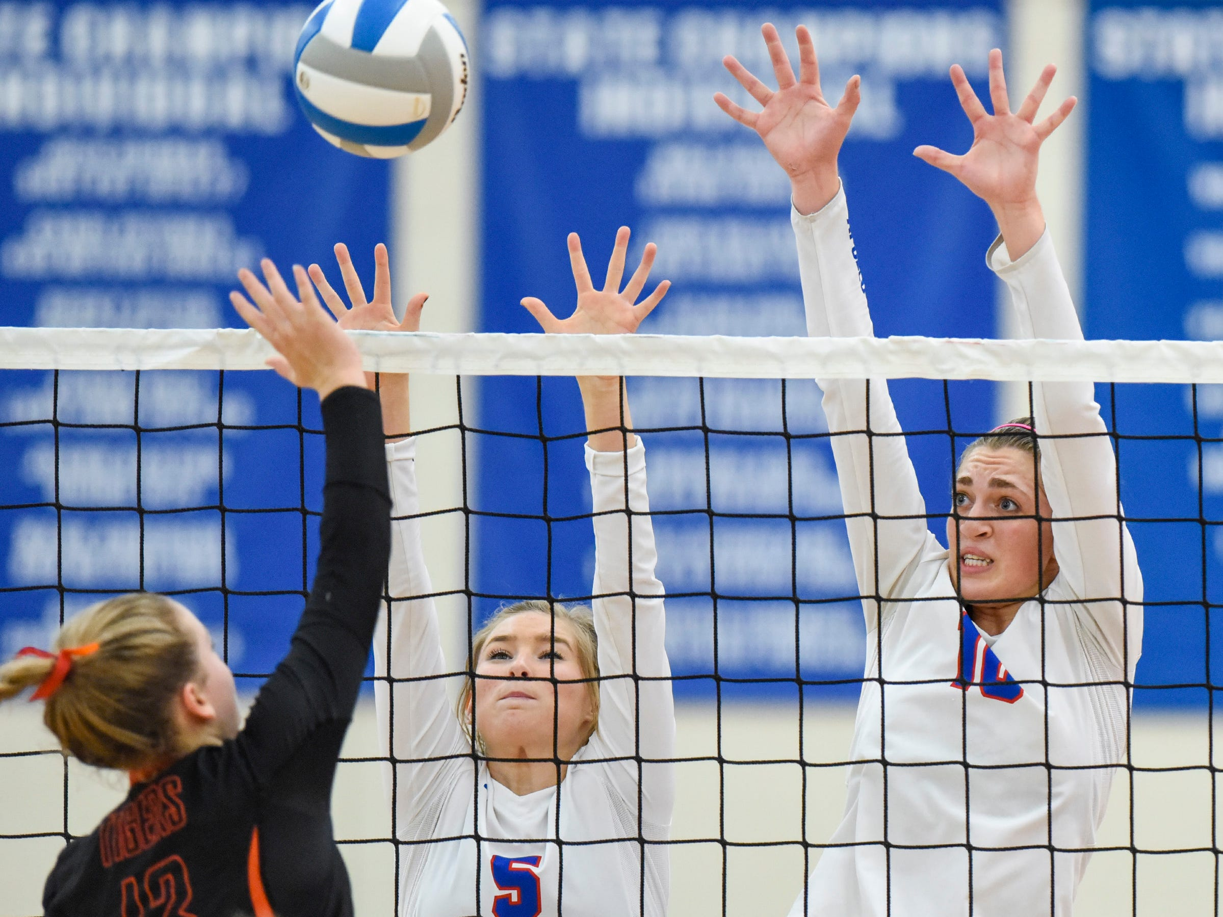 Tech's Megan Raygor tries to spike the ball past Apollo's Rhian Smith and Haley Schleper during the second game Tuesday, Oct. 2, at Apollo High School.