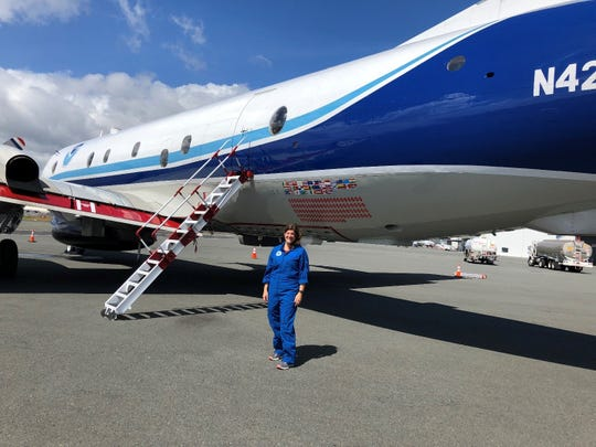 Heather Holbach standing next to the Lockheed WP-3D Orion aircraft used for tracking hurricanes.