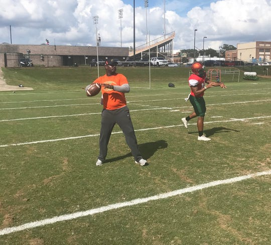 FAMU head coach Willie Simmons can still throw laser passes. He works on warm-up drills with the quarterbacks.
