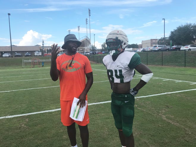 Wide receivers coach Jelani Berassa discusses routes with Chad Hunter.
