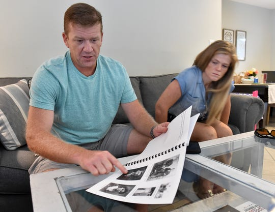 Brian Roberson (left), of Ocala, and Kaley Stone, two of the four children of the late Susan Roberson, look over photos of their grandparents in a book on the history of Oslo written by their grandfather, Susan Roberson's father Arnold Helseth, while discussing memories of their mother and family history on Tuesday, Oct. 2, 2018, at Stone's home in Indian River County. Susan Roberson was killed in a traffic accident on Oslo Road at the intersection with Citrus Springs Road on Friday, Sept. 28, 2018, in Indian River County.