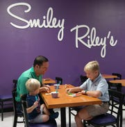 Anthony Astrup and sons Austin (7) and Alex (2) enjoy ice cream and some of the shop's challenging puzzles and games.